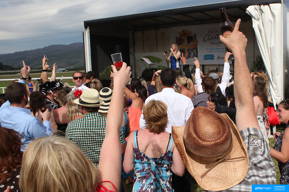 Race goers drink and dance to a live country singer during a day at the Races at the Cromwell Race meeting, Cromwell, Central Otago, New Zealand. 27th November 2011. Photo Tim Clayton