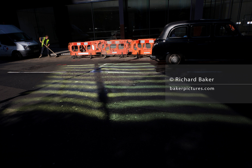 Roadworks and stripes from an adjacent office building reflects on to the road surface in Threadneedle Street, City of London.
