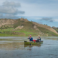 two men paddling a green pakboat canoe down the wild and senic missouri river, umrbnm, russel country, montana, usa, upper missouri river breaks national monument, russell