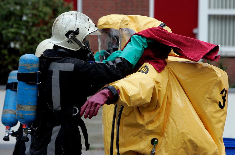 Foto: Gerrit de Heus. Scheveningen. 31/10/05. Hotel Bilderberg ontruimd, nadat er schadelijke stoffen waren vrijgekomen. Een medewerker van de brandweer wordt door een collega geholpen met het schoonmaken van zijn beschermende pak, voordat hij dat uit kan trekken.