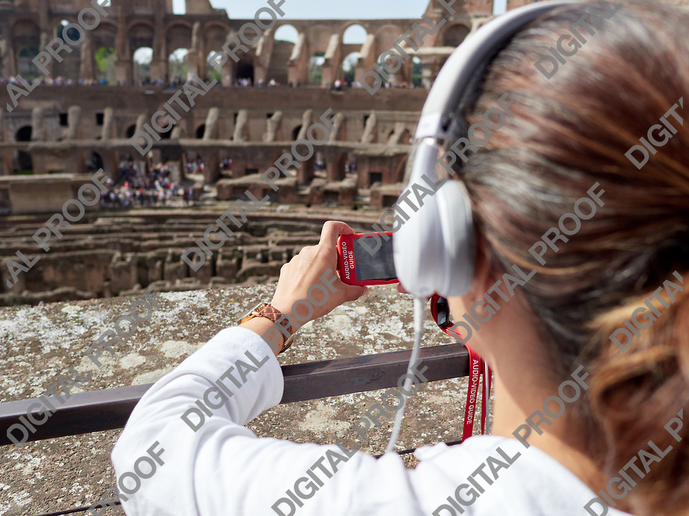 Tourist women listen the audioguide while visiting the Colosseum