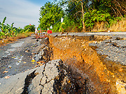 14 JULY 2015 - THAILAND:  A road that has collapsed from subsidence in Pathum Thani province. The drought that has crippled agriculture in central Thailand is now impacting residential areas near Bangkok. The Thai government is reporting that more than 250,000 homes in the provinces surrounding Bangkok have had their domestic water cut because the canals that supply water to local treatment plants were too low to feed the plants. Local government agencies and the Thai army are trucking water to impacted communities and homes. Roads in the area have started collapsing because of subsidence caused by the retreating waters. Central Thailand is contending with drought. By one estimate, about 80 percent of Thailand's agricultural land is in drought like conditions and farmers have been told to stop planting new acreage of rice, the area's principal cash crop.      PHOTO BY JACK KURTZ