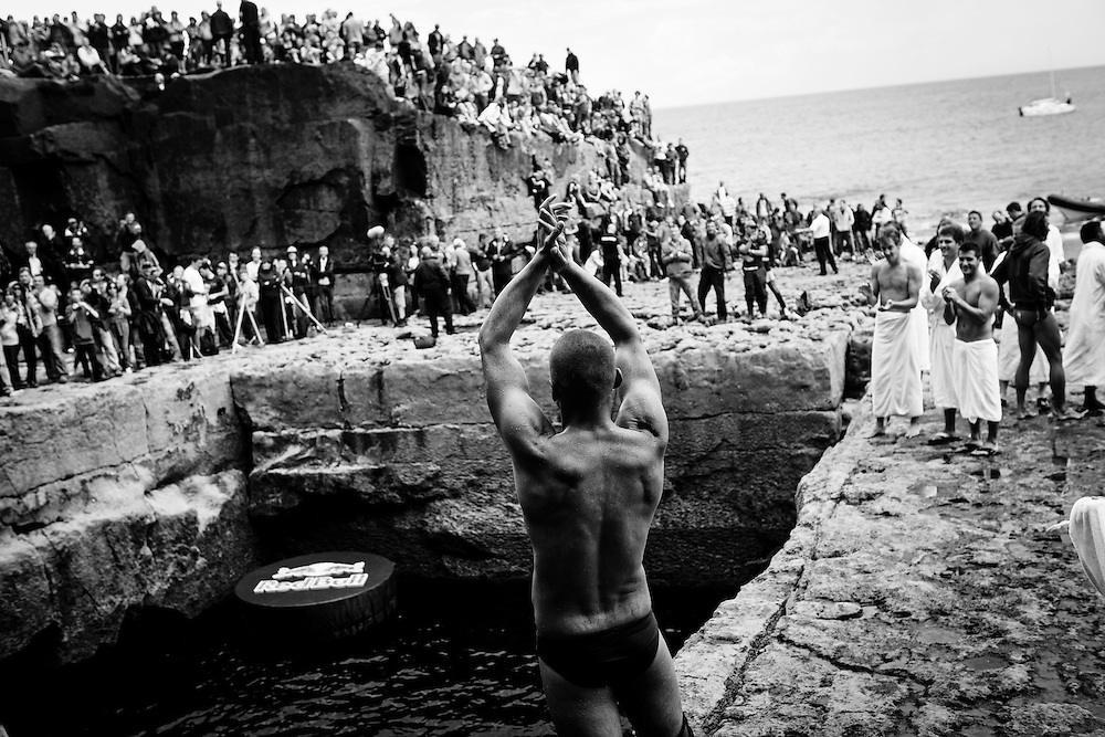 Russian high diver Artem Silchenko, celebrates a dive on the edge of the Serpent's Lair. The Red Bull Cliff Diving World Series 2012, Inis Mor, Ireland. 04 August 2012