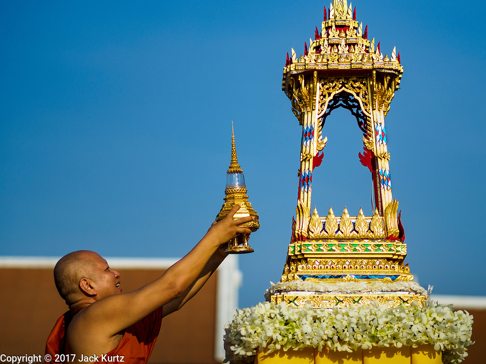 """03 NOVEMBER 2017 - BANGKOK, THAILAND: The abbot of Wat Prayurawongsawat on the Thonburi side of the Chao Phraya River, puts up a lantern for Loi Krathong. Loi Krathong is translated as """"to float (Loi) a basket (Krathong)"""", and comes from the tradition of making krathong or buoyant, decorated baskets, which are then floated on a river to make merit. On the night of the full moon of the 12th lunar month (usually November), Thais launch their krathong on a river, canal or a pond, making a wish as they do so. Loi Krathong is also celebrated in other Theravada Buddhist countries like Myanmar, where it is called the Tazaungdaing Festival, and Cambodia, where it is called Bon Om Tuk.     PHOTO BY JACK KURTZ"""