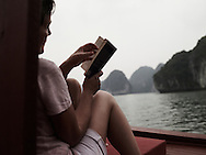 A caucasian woman is reading on the deck of a traditional junk sailing in calm waters of Ha Long bay, A UNESCO world heritage site. Vietnam, Asia