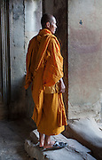 Buddhist monk in orange robe at Angkor temple (Cambodia)