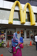 Malaysia, Kuala Lumpur. Veiled woman with baby in front of McDonald's at Bukit Bintang shopping and entertainment district.