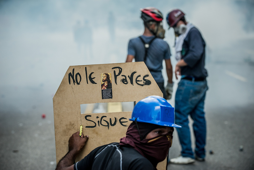 CARACAS, VENEZUELA - MAY 20, 2017:  Anti-government protesters use homemade shields and throw rocks and molotov cocktails at members of the National Police, who responded by heavily tear gassing and firing rubber bullets and buckshot at them.  The streets of Caracas and other cities across Venezuela have been filled with tens of thousands of demonstrators for nearly 100 days of massive protests, held since April 1st. Protesters are enraged at the government for becoming an increasingly repressive, authoritarian regime that has delayed elections, used armed government loyalist to threaten dissidents, called for the Constitution to be re-written to favor them, jailed and tortured protesters and members of the political opposition, and whose corruption and failed economic policy has caused the current economic crisis that has led to widespread food and medicine shortages across the country.  Independent local media report nearly 100 people have been killed during protests and protest-related riots and looting.  The government currently only officially reports 75 deaths.  Over 2,000 people have been injured, and over 3,000 protesters have been detained by authorities.  PHOTO: Meridith Kohut