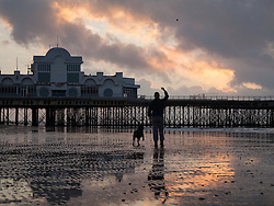 © Licensed to London News Pictures. 04/10/2016. Southsea, Hampshire, UK.  A woman throws a ball for her dog as dawn breaks over South Parade Pier in Southsea this morning, 4th October 2016. Today will be another dry and sunny, but breezy, autumn day in the south of England. Photo credit: Rob Arnold/LNP