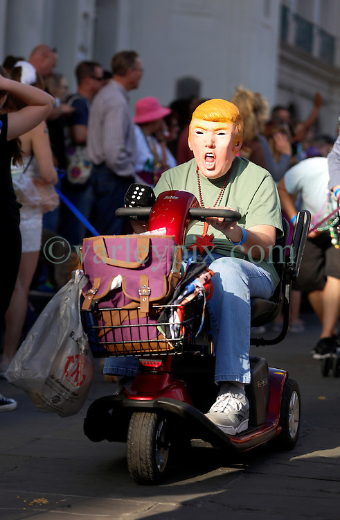 31 January 2016. New Orleans, Louisiana.<br /> Mardi Gras Dog Parade. A man in a Donald Trump face mask rolls a disability scooter past the St louis Cathedral. The Mystic Krewe of Barkus winds its way around the French Quarter with dogs and their owners dressed up for this year's theme, 'From the Doghouse to the Whitehouse.' <br /> Photo©; Charlie Varley/varleypix.com