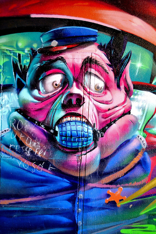 Cartoonish Pink Cop with Bulging Eyes and Mouth Gag Mural in Eger, Hungary<br /> In an underpass near the Castle of Eger, Hungary, is this cartoonish pink cop with bulging eyes and mouth gag mural. It must have some significance but I am not sure what it means or represents.