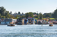 Fisherman's Wharf in Victoria, BC on a sunny summer day is busy with harbour ferries and visitors and is famous for colorful floathomes.
