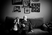 Dolores and James Hart sit on a couch and take pictures of their grandchildren and great-grandchildren after both had surgery to their eyes that restored their vision and enabled them to see the family they created at one of the last family parties James attended before his death. James passed away a week before his 64th wedding anniversary with Dolores and would be buried in the same outfit he wore the day the photograph was taken.