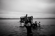 Rescuers help migrants landing on the shores of the Greek island of Lesbos after crossing the Aegean Sea from Turkey on November 16, 2015. Since the start of the summer, the Greek island of Lesbos has assumed notoriety as the main gateway into Europe for thousands of desperate refugees that continue to cross the Aegean sea from Turkey every day.