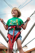 "Boy/girl ""fly/ride"" on the bungee trampoline at Mountain Village Heritage Plaza, Telluride Village, Colorado, USA"
