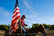 16 JULY 2020 - BOONE, IOWA: A woman with an American flag in the horse show arena on the first day of the Boone County Fair in Boone. Summer is county fair season in Iowa. Most of Iowa's 99 counties host their county fairs before the Iowa State Fair. In 2020, because of the COVID-19 (Coronavirus) pandemic, many county fairs were cancelled, and most of the other county fairs were scaled back to concentrate on 4H livestock judging. Boone county scaled back its fair this year. The Iowa State Fair was cancelled completely. Boone County Emergency Management did not approve going ahead with the fair, and has advised anyone who goes to the fair to take precautions and monitor themselves for symptoms of the Coronavirus.         PHOTO BY JACK KURTZ