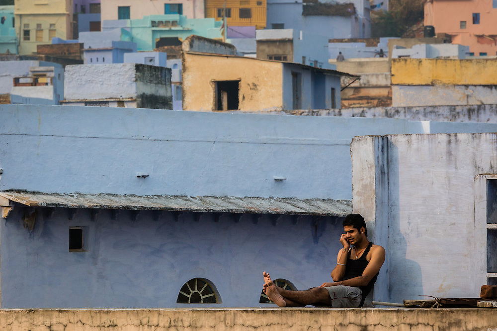 On the rooftops of Bundi, a man is taking a mobile phone call, while sitting relaxed.