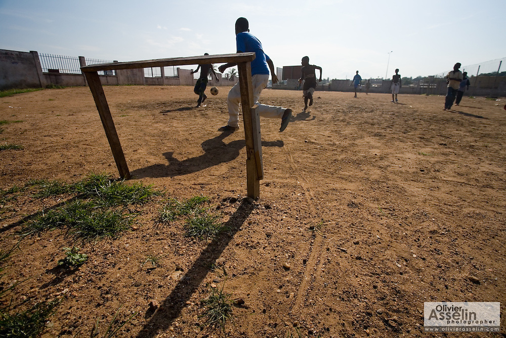 Children playing football on dirt field, Accra, Ghana, 2006.