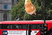 London, UK: The inflatable balloon called Baby Trump flies above the statue of wartime Brish Prime Minister Winston Churchill in Parliament Square, Westminster, the seat of the UK Parliament, during the US President's visit to the UK, on 13th July 2018, in London, England. Baby Trump is a 20ft high orange blimp depicting the US President as an enraged, smartphone-clutching infant - and given special permission to appear above the capital by London Mayor Sadiq Khan because of its protest rather than artistic nature. It is the brainchild of Graphic designer Matt Bonner. Photo by Richard Baker / Alamy Live News