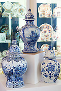 Delft Blue luxury old hand-painted porcelain goods - urns and vases - at Royal Delft Experience shop in Amsterdam, Holland