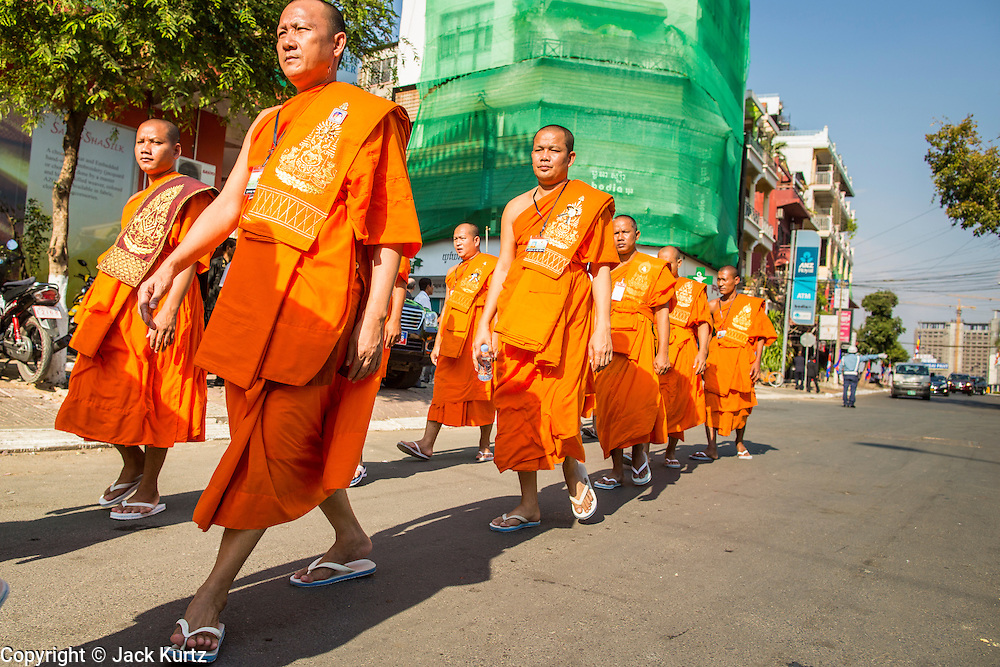 """04 FEBRUARY 2013 - PHNOM PENH, CAMBODIA: Cambodian Buddhist monks walk to the cremation venue for the cremation of King-Father Norodom Sihanouk in Phnom Penh. Norodom Sihanouk (31 October 1922- 15 October 2012) was the King of Cambodia from 1941 to 1955 and again from 1993 to 2004. He was the effective ruler of Cambodia from 1953 to 1970. After his second abdication in 2004, he was given the honorific of """"The King-Father of Cambodia."""" Sihanouk died in Beijing, China, where he was receiving medical care, on Oct. 15, 2012.    PHOTO BY JACK KURTZ"""