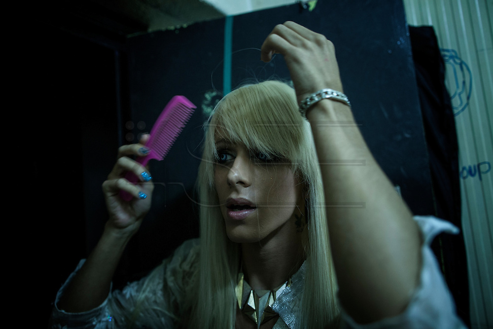 A young travesti brushing his wig