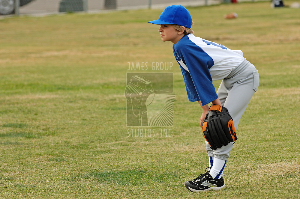 A young boy as catcher in the outfield in baseball little leagues