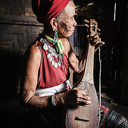 Old Kayah woman playing a sort of guitar, Loikaw area, Myanmar, Asia