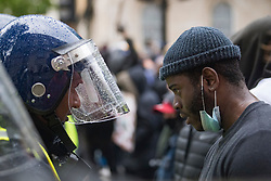 © Licensed to London News Pictures. 06/06/2020. London, UK. A protesters comesfaceto face with a policeofficerin Riot gear, in Westminster, central London while taking part in a Black Lives Matter demonstration over the killing of African American George Floyd. The death of George Floyd, who died after being restrained by a police officer In Minneapolis, Minnesota, caused widespread rioting and looting across the USA. Photo credit: Ben Cawthra/LNP