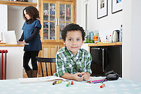 Portrait of boy (5-6) sitting at table mother using laptop in background