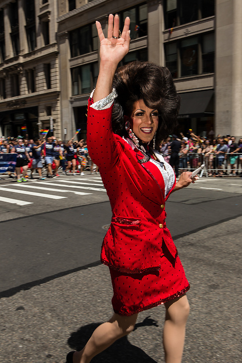 New York, NY - 25 June 2017. New York City Heritage of Pride March filled Fifth Avenue for hours with groups from the LGBT community and it's supporters. A marcher likely to be a drag queen in a bright red suit and a giant bouffant wig.