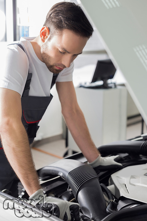 Full length side view of male mechanic examining car engine in repair shop