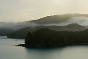Yacht at anchor in a secluded cove in the Bay of Islands, New Zealand.