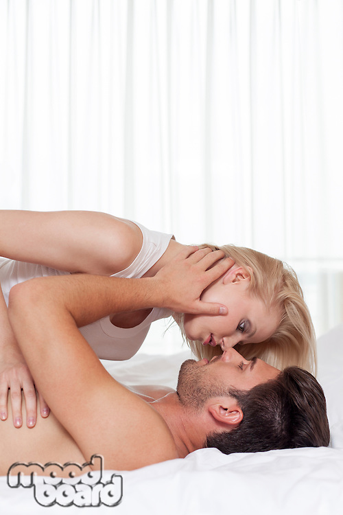 Side view of affectionate young couple in hotel room