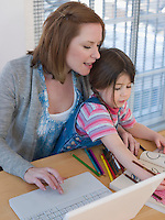 Mother Using Laptop While Daughter Colors