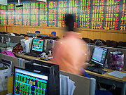 02 SEPTEMBER 2013 - BANGKOK, THAILAND: A woman walks in to watch real time stock results at Asia Plus Securities headquarters in central Bangkok. The Thai stock market has declined more than 20% from its 2013 high as data as Thailand entered a recession in the second quarter. The loss of value in the Stock Exchange of Thailand (SET) is the greatest sell off since the end of the Asian financial crisis in 1998. Foreign investors have sold more than $1 billion of local shares this month amid signs of slowing regional economic growth and speculation that the U.S. Federal Reserve will soon cut its stimulus.      PHOTO BY JACK KURTZ