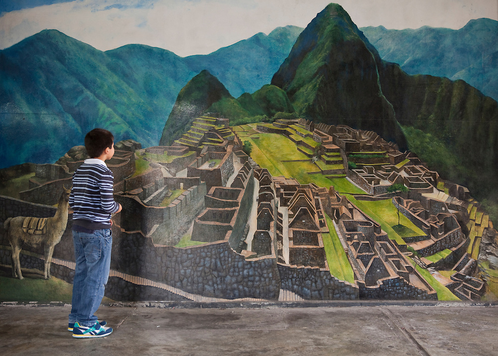 Boy watching a mural with a painting of Machu Picchu, at a market in Lima, Peru.