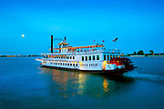 Steamboat carries tourists on a twilight tour up the Misissippi River in New Orleans.