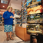 Buying Greek Olympic tourist trinkets, Athens. Lady tourists select holiday souvenirs in Plaka shopping centre, the largest official Olympic merchandising outlet, down town Athens. The 29th modern Olympic circus came home to Greece in 2004 and the birthplace of athletics was among the woodland of Ancient Olympia where for 1,100 continuous years, the ancients held their pagan festival of sport and debauchery. The modern games share many characteristics with its ancient counterpart. Corruption, politics and cheating interfered then as it does now and the 2004 Athens Olympiad will echo both what was great and horrid about the past.