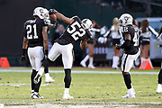 Oakland Raiders cornerback Sean Smith (21) and Oakland Raiders rookie strong safety Karl Joseph (42) look on as Oakland Raiders defensive end Khalil Mack (52) celebrates after making a late fourth quarter strip sack and fumble recovery that effectively ends the 2016 NFL week 12 regular season football game against the Carolina Panthers on Sunday, Nov. 27, 2016 in Oakland, Calif. The Raiders won the game 35-32. (©Paul Anthony Spinelli)