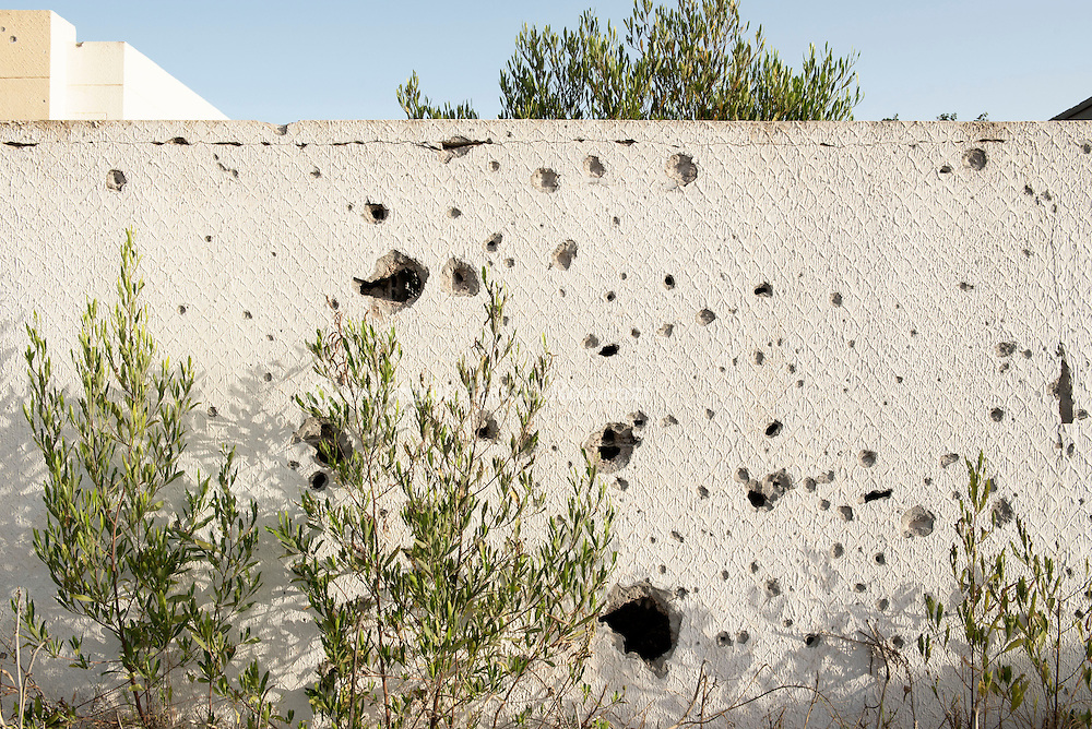 Libya: Particular of a riddled by shrapnels wall in 700 neighbourhood in Sirte. Alessio Romenzi