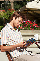 Young Man at Outdoor Cafe reading guidebook