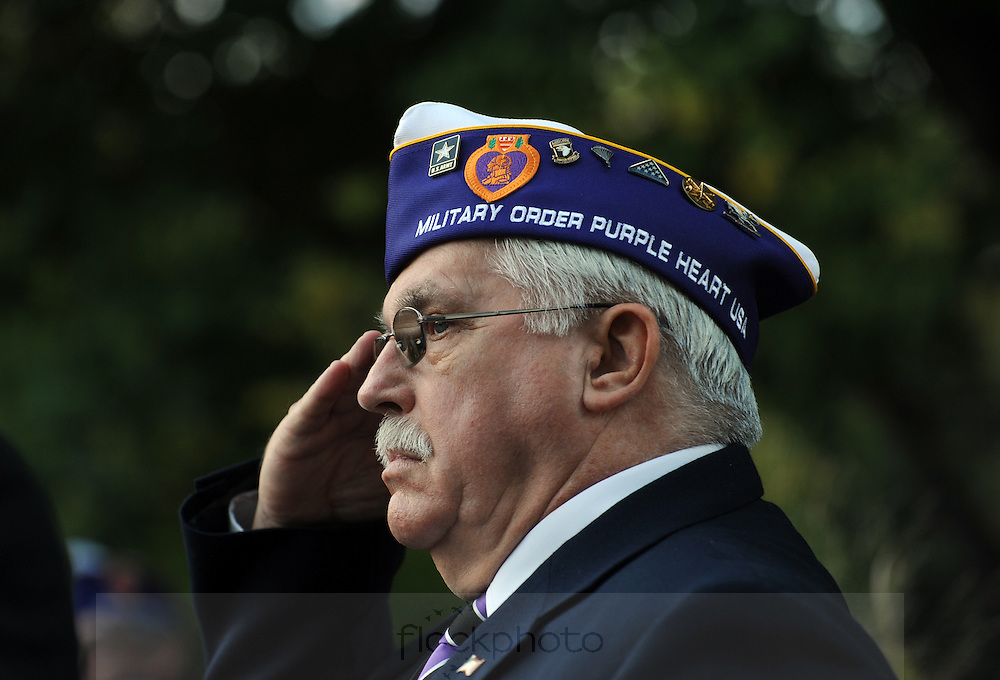 Tony Payne, Purple Heart recipient and State Adjutant of the Military Order of the Purple Heart, stands at attention during a ceremony awarding Watertown the official designation of a Purple Heart Community, Oct. 13, 2015.
