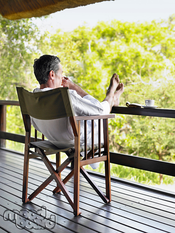 Adult man in bathrobe sitting on chair at terrace with feet up