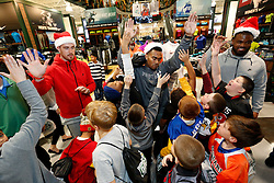 "Kansas City Chiefs players, Travis Kelce, Charcandrick West and Dontari Poe celebrate with members of the Football and Cheerleading Club of Johnson County after shopping for items on their ""wish list"" at the ""Sports Matter"" Holiday Shopping event hosted by DICK'S Sporting Goods on Thursday, Dec. 17, 2015, in Leawood, KS. (Colin E. Braley/AP Images for Dick's Sporting Goods)"