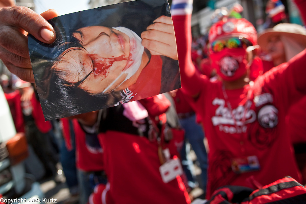 Apr. 12, 2010 - BANGKOK, THAILAND: Red Shirt protestors hold up a photo of a person killed in the street protests Saturday in front of the Prime Minister's house on Soi 31 off of Sukhumvit Rd in Bangkok Monday. The funeral cortege for the Red Shirts killed in the violent crackdown Saturday wound through Bangkok and parts of the procession passed by the Prime Minister's home. Thousands of mourners came out to pay respects for dead Red Shirts. 21 people, including 16 Thai civilians were killed when soldiers tried to clear the Red Shirts' encampment in Bangkok. Thousands more came out to call for the government of Thai Prime Minister Abhisit Vejjajiva to step down. Today Gen. Anupong Paojinda, the Chief of Staff of the Thai Army, reiterated that the Army would not use violence to break up the protests and joined the call for the Prime Minister to call new elections. This is the beginning of Songkran, Thai New Year's week, and the government has cancelled the official festivities fearing more violence. It was during last year's Songkan festivities that the Thai Army and police used force to break up the Red Shirt protests. That protest is now called the Songkran Riots.         Photo By Jack Kurtz
