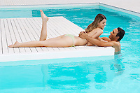Man in pool hugging girlfriend on pool deck side view