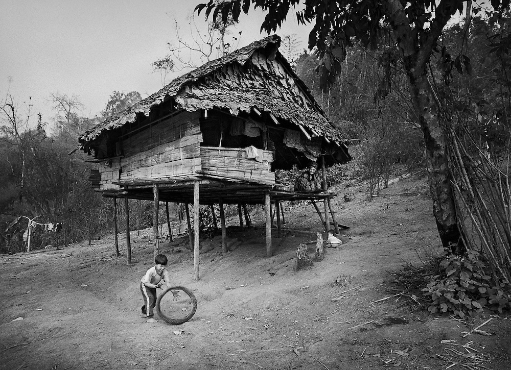 A young Karen boy plays outside his house, watched by his mother, in the Lep Per Her camp. <br /> <br /> After the previous camp was burnt down by the Burmese military in 2002, the occupants were forced to live on the banks of the Moei river, being restricted in crossing into Thailand by the Thai military. <br /> <br /> Even so, the teachers insisted that the children continue with their schoolwork and still held school every day. &quot;We do our best and sacrifice all that we can because we have a vision for all these children to become educated people&quot; (volunteer teacher for IDP children).