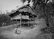 A young Karen boy plays outside his house, watched by his mother, in the Lep Per Her camp. <br />