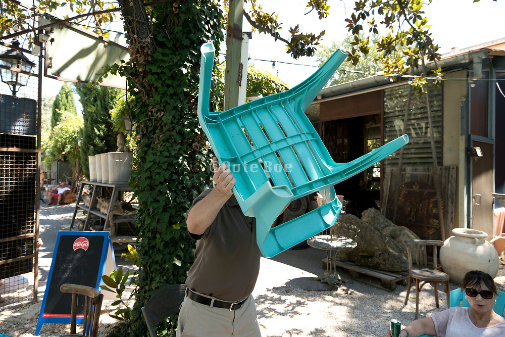 moving a plastic chair at an outdoors garden cafe terrace